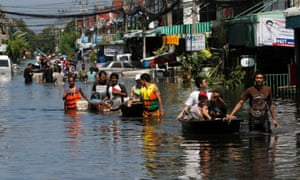 People push their belongings through the water during an evacuation from a flooded area in Bangkok in 2011.