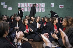 Lyon, France: Lawyers sit on the floor in a courthouse, in front of posters referring to the justice minister, Nicole Belloubet, that read: 'Belloubet killed me'. Magistrates and lawyers are protesting against the government's plans to end the special retirement system for lawyers and others in the legal sector