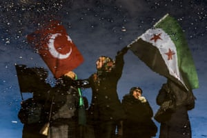 Istanbul, Turkey: A reflection shows a woman waving Turkish and Free Syrian flags