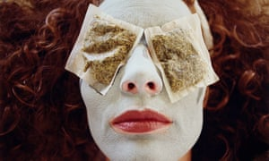 Woman wearing face mask and tea bags over eyes