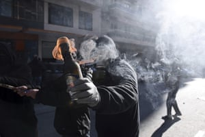 A hooded youth prepares to throw a petrol bomb at riot police in the northern Greek city of Thessaloniki during the rally commemorating the killing of a 15-year old student in 2008.