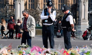 Police officers stop to look at floral tributes to the victims of the 22 March terror attack in Westminster.