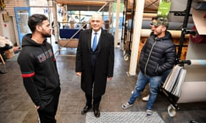 Sajid Javid walks around the building, now a carpet shop, where his parents once worked during a visit to his former home at Stapleton Road in Bristol.