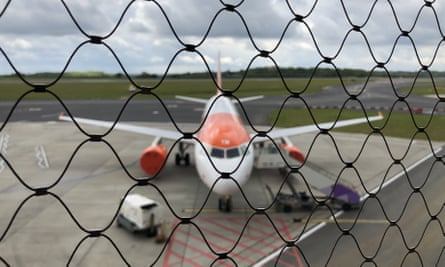 A plane behind a fence at Luton airport