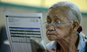 A woman looks at a ballot paper during mid-term elections in Manila on May 13, 2013.