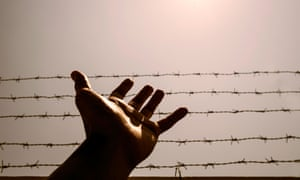 A hand and barbed wire