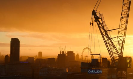 The sun sets behind a construction crane showing the branding of British construction company Carillion.