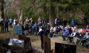 Descendants of slave owners, slaves and freed slaves listen to a history of the plantation. Eve Wayne is seated near the center, in cream colored coat.