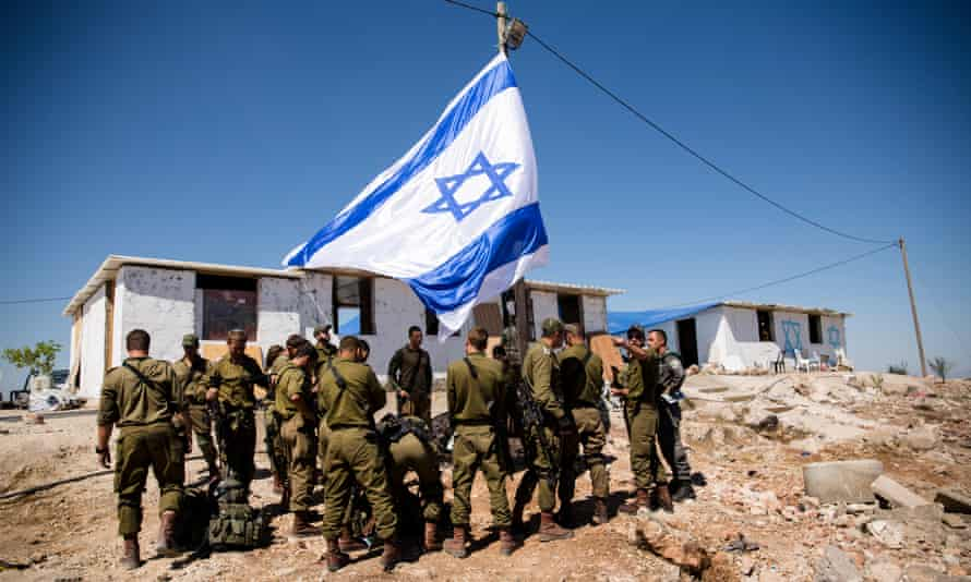 Members of the Israeli defence forces gather for a briefing as they take control of the recently established outpost of Evyatar in the West Bank.