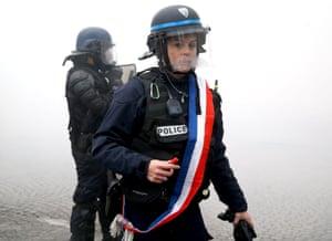 A policewoman wearing a tricolour sash braves the teargas.