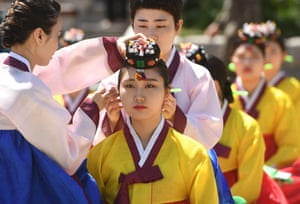 A woman wears a traditional flower cap during a coming-of-age ceremony in Seoul, South Korea