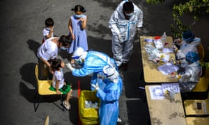 A medical worker swabs throat of a child for nucleic acid test in Urumqi, Xinjiang. The city reported no new cases on 16 August.