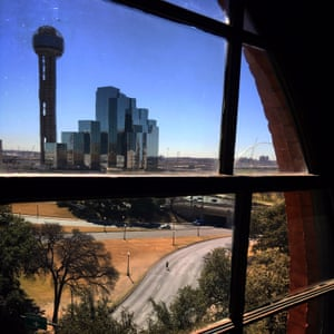 A tourist walks into the middle of Elm Street in Dallas where the third and final shot fired by Lee Harvey Oswald struck John F Kennedy in the back of the head, killing him instantly. Photographed from the window next to the window that Lee Harvey Oswald shot from inside the Texas School Book Depository. (The actual window is blocked from general access)