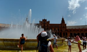 People refresh themselves in a fountain at Plaza de Espana, Seville, as temperatures climb to the mid-40s.