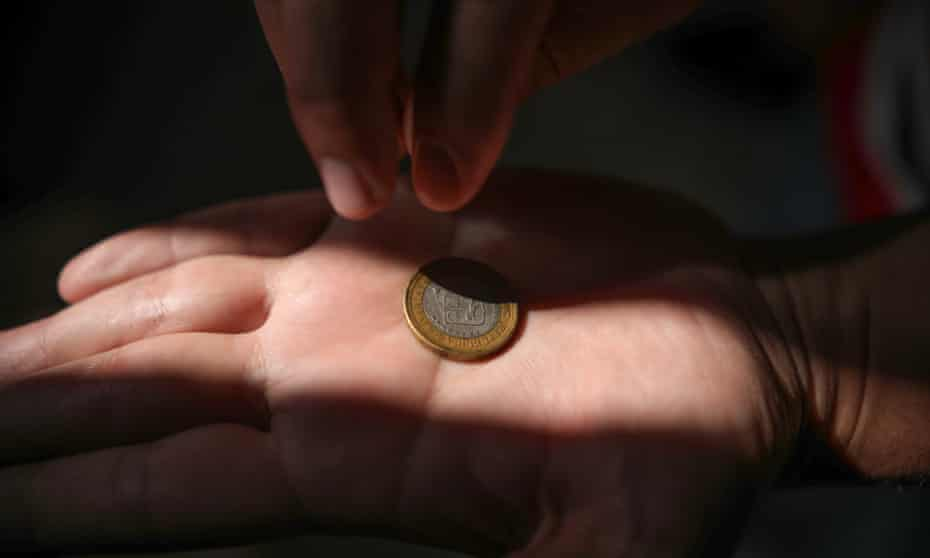 A Venezuelan asylum seeker in Mexicali holds one of the few possessions they escaped their home with earlier this year - a worthless bolívar coin
