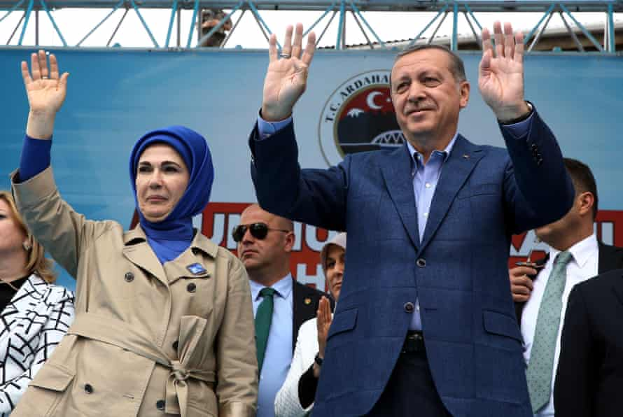 Turkey's leader Recep Tayyip Erdogan and his wife, Emine, salute supporters.