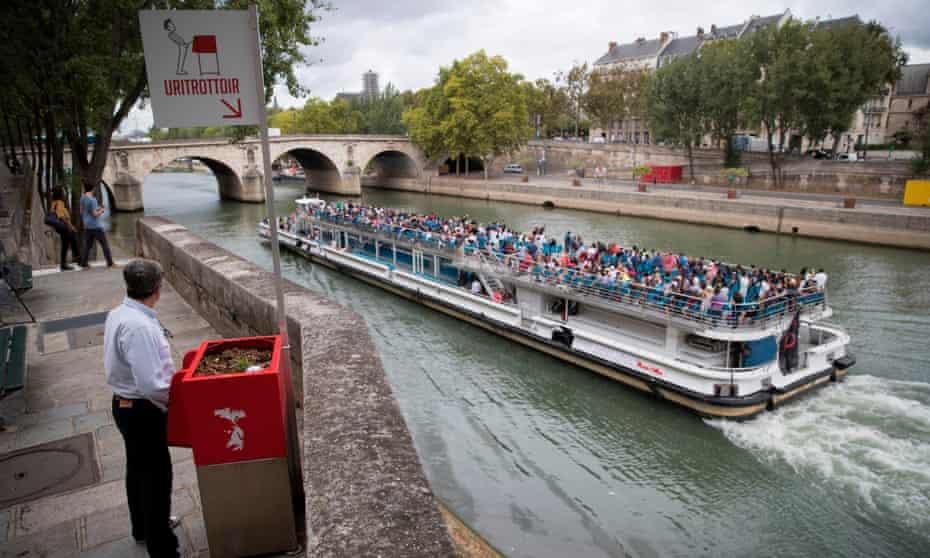 A man stands at a public 'pissoir' on Île Saint-Louis in Paris.