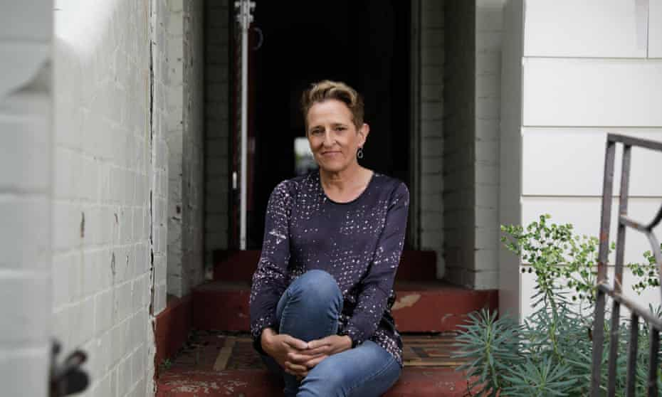 a woman with short hair in jeans and a dark coloured jumper sits on the stairs outside a white weatherboard house