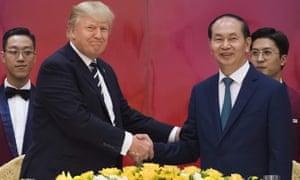 Vietnamese President Tran Dai Quang shakes hands with Donald Trump in Hanoi.