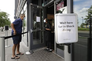 A customer, left, is greeted by a worker, right, at the entrance to a Shake Shack restaurant, last month.