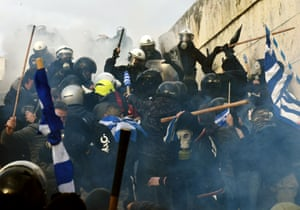 Protesters with wooden poles clash with riot police wielding batons in Athens