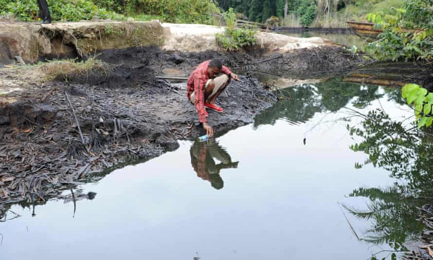 A man scoops oil from a river in southern Nigeria