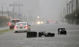 Vehicles head down a flooded Tulane Avenue as heavy rain falls on Wednesday in New Orleans.