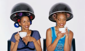 Two women under hairdryers, wearing rollers