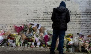 A young man looks at messages and flowers left at the scene in Hackney where 18 year old Israel Ogunsola was stabbed to death