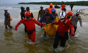 Rescue workers carry a body bag at Tanjung Lesung beach.