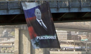 In this photo provided by Gothamist.com, a banner depicting the Russian president, Vladimir Putin, and labelling him a 'peacemaker' hangs from the Manhattan Bridge in New York on Thursday.
