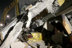 A flattened taxi is seen under the debris of a collapsed hotel in Portoviejo as heavy machinery works at the site