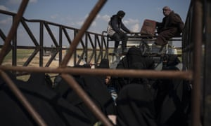 Men, women and children ride in the back of a truck leaving Baghouz