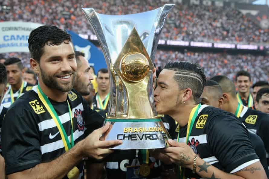 Felipe holds the Brasileirao trophy while his Corinthians teammate Luciano gives it a kiss.