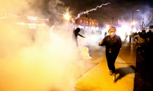 Protesters run from a cloud of tear gas in Ferguson