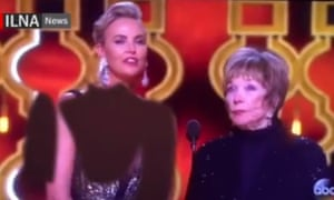 Charlize Theron, standing next to Shirley MacLaine, whose outfit was not digitally manipulated, moves away from the photoshopped sleeves and neckline on her dress at the Oscars.