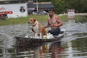Ryan Sizemore paddles down Highway 61 with his dog Rico amid flooding from the Mississippi River