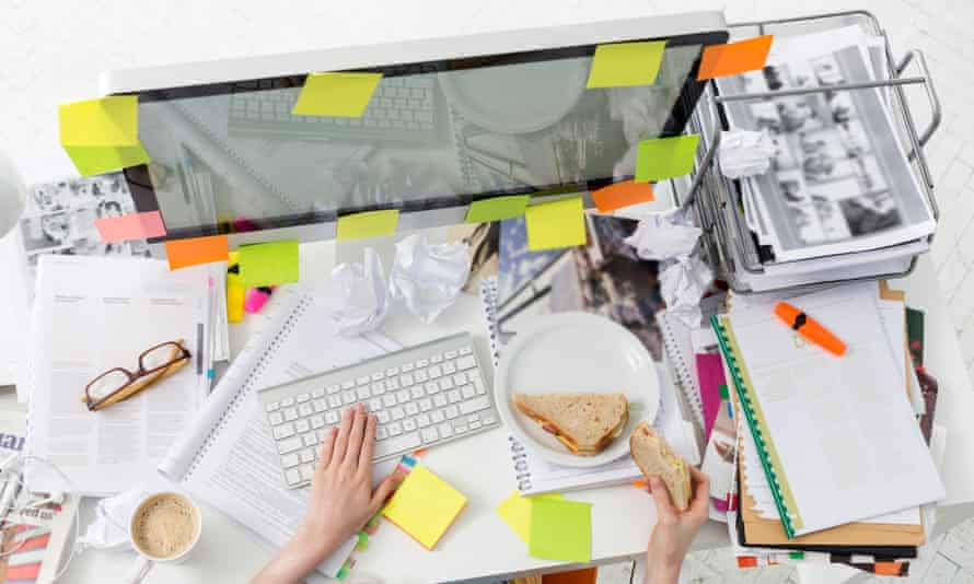 Office worker at messy office desk eating a sandwich