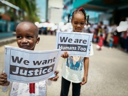 Anak-anak berdemonstrasi di luar hotel kumuh yang telah menjadi rumah mereka selama bertahun-tahun.  Akomodasi ini diatur oleh Organisasi Internasional untuk Migrasi, yang mengandalkan dana pemerintah Australia.