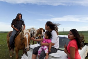 Angel Rose Lookinghorse, sitting with her younger cousins, Linda Lookinghorse and Maryann Lara, as she speaks to her brother, Jayden Lookinghorse, riding his horse, on the Cheyenne River Reservation in Green Grass, South Dakota.