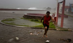 A man runs from a wave at the waterfront in Baracoa, Cuba.