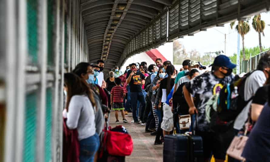 Migrants wait in line to cross the border at the Gateway International Bridge into the US from Matamoros, Mexico to Brownsville, Texas, on 15 March 2021.