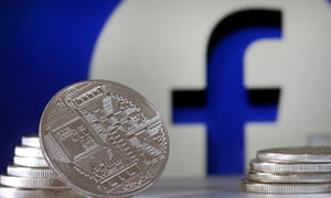 New cryptocurrency Libra coins with the Facebook logo in the background.