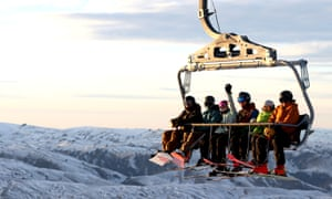 Skiers and snowboarders ride chairlifts on opening day in Cardrona, New Zealand