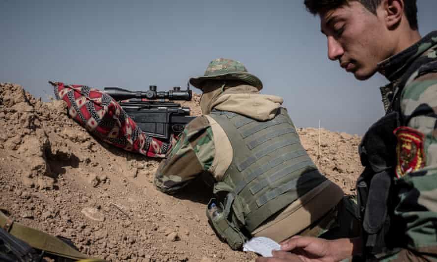 A Syrian Kurdish peshmerga sniper takes aim