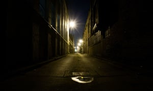 A dark brick alley at night with street light in background