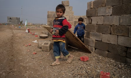 Children in Fallujah emerge from the garden of an abandoned house that has not been swept for unexploded ordnance