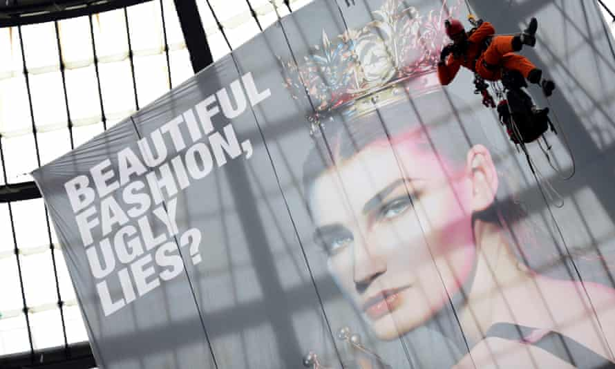 A Greenpeace activist raises a banner to protest against the use of toxic chemicals in clothing.