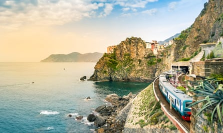 The Cinque Terre - train station in small village with colorful houses on cliff overlooking sea.
