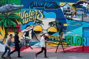 People pass by a mural at the launch of the 'Visit Lauderdale x London Art Swap.'